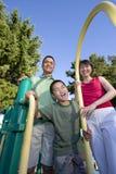 Famiglia sul campo da giuoco che sorride - verticale fotografia stock