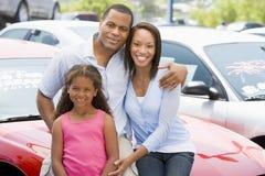 Famiglia sul nuovo lotto dell'automobile Immagine Stock Libera da Diritti