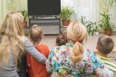 Famiglia sul pavimento alla TV fotografia stock libera da diritti