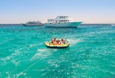 Famiglia sul tubo in acqua che è rimorchiata in barca Fotografia Stock Libera da Diritti