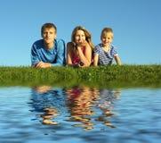 Famiglia sull'erba con acqua immagini stock
