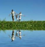 Famiglia sull'erba sotto cielo blu Fotografia Stock Libera da Diritti