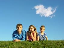 Famiglia sull'erba sotto cielo blu Fotografie Stock Libere da Diritti