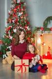 Famiglia sulla notte di Natale al camino Bambini che aprono i presente di natale Bambini sotto l'albero di Natale con i contenito fotografia stock