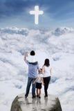 Famiglia sulla scogliera ed esaminare il segno trasversale Immagine Stock