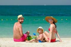 Famiglia sulla spiaggia Bambino che gioca con la madre ed il padre Immagini Stock
