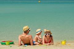 Famiglia sulla spiaggia Bambino che gioca con la madre ed il padre Immagine Stock