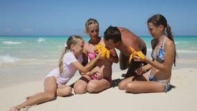 Famiglia sulla spiaggia che mangia la frutta del mango video d archivio