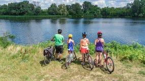 Famiglia sulle bici che ciclano all'aperto, sui genitori attivi e sui bambini sulle biciclette, vista aerea della famiglia felice immagini stock