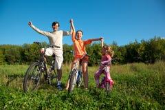 Famiglia sulle biciclette in giorno pieno di sole della sosta Fotografia Stock