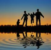Famiglia sullo stagno di tramonto Fotografie Stock Libere da Diritti