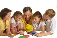 Famiglia sveglia dei cinque che giocano sul bianco Immagini Stock