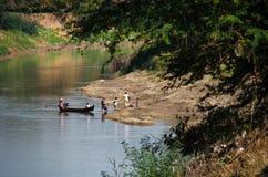 Famiglia in trasporto tradizionale in barca nella zona rurale in mio immagini stock libere da diritti