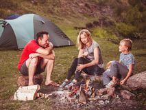 Famiglia vicino al falò nella foresta Immagini Stock