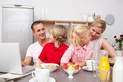 Famiglia vivace che mangia prima colazione insieme Immagine Stock