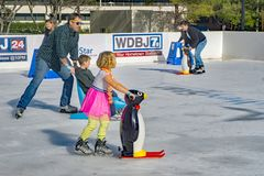 Famiglie che imparano al pattinaggio su ghiaccio fotografia stock