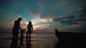 Famil que camina en un lago en la puesta del sol Las siluetas del los peque?os ni?os y los padres miden el tiempo juntas despu?s, almacen de video