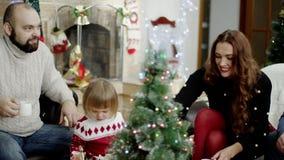 Familes felices que se sientan alrededor de abeto y de té de consumición en la fiesta de Navidad almacen de video