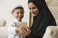 Familia árabe, madre árabe e hijo que usa el teléfono móvil foto de archivo