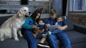 Familia étnica de Mulit con el perro casero que descansa sobre el sofá almacen de metraje de vídeo