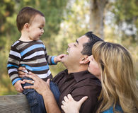 Familia étnica feliz de la raza mezclada que juega en el parque fotos de archivo libres de regalías