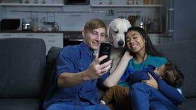 Familia étnica multi con el perro casero que presenta para el selfie almacen de video