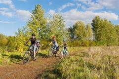 Familia activa en las bicis que completan un ciclo al aire libre Fotos de archivo libres de regalías