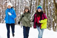 Familia activa - madre y funcionamiento de los niños al aire libre en parque del invierno Imágenes de archivo libres de regalías
