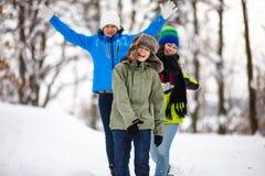 Familia activa - madre y funcionamiento de los niños al aire libre en parque del invierno Foto de archivo libre de regalías