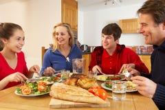 Familia adolescente que come el almuerzo junto en cocina Foto de archivo