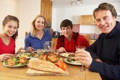 Familia adolescente que come el almuerzo junto en cocina Imagen de archivo