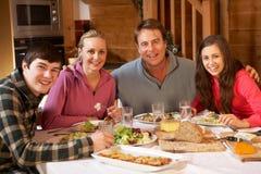 Familia adolescente que disfruta de la comida en chalet alpestre Fotografía de archivo libre de regalías