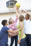 Familia adolescente que juega a baloncesto fuera del garaje Fotos de archivo libres de regalías
