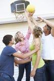 Familia adolescente que juega a baloncesto fuera del garaje Foto de archivo libre de regalías