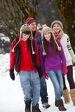 Familia adolescente que recorre adelante en estación de esquí Imagen de archivo libre de regalías