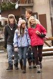 Familia adolescente que recorre a lo largo de la calle en estación de esquí Imagen de archivo