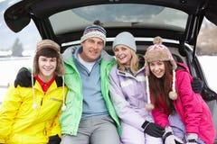 Familia adolescente que se sienta en el cargador del programa inicial del coche Fotos de archivo libres de regalías