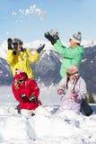 Familia adolescente que tiene lucha de la nieve en montañas Foto de archivo libre de regalías