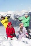 Familia adolescente que tiene lucha de la nieve en montañas Imagenes de archivo