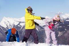 Familia adolescente que tiene lucha de la nieve en montañas Imágenes de archivo libres de regalías
