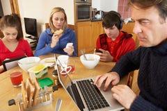 Familia adolescente usando los adminículos mientras que come Imagenes de archivo
