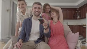 Familia adorable feliz del retrato que ve la TV en casa junto El padre sostiene el telecontrol y cambia los canales, almacen de metraje de vídeo
