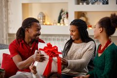 Familia africana para la Navidad con el regalo imagen de archivo