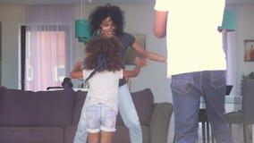 Familia africana que se divierte que ríe jugando el escondite junto almacen de video
