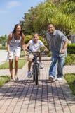 Familia afroamericana con la bici del montar a caballo del muchacho y padres felices foto de archivo libre de regalías