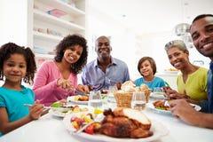 Familia afroamericana de la generación multi que come la comida en casa Foto de archivo libre de regalías