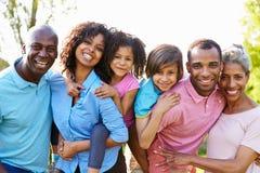 Familia afroamericana de la generación multi que se coloca en jardín