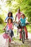 Familia afroamericana en paseo del ciclo en campo Fotos de archivo
