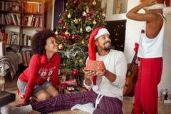 Familia afroamericana feliz que intercambia los regalos delante del árbol de navidad adornado imagenes de archivo