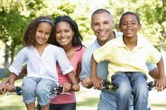 Familia afroamericana joven que completa un ciclo en parque foto de archivo